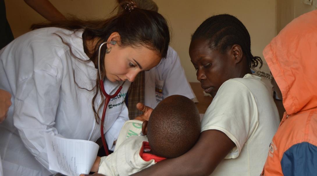Interna francesa revisa a un niño durante sus prácticas de enfermería en Tanzania.
